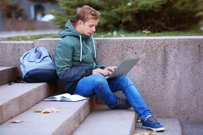 Adolescente con il computer portatile che si siede sui punti fotografia stock