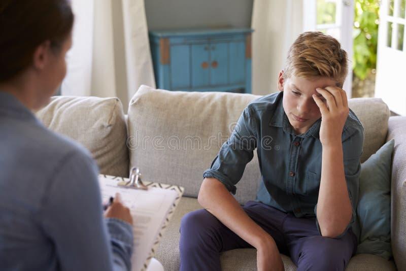 Adolescente con il problema che parla con il consulente a casa immagine stock libera da diritti