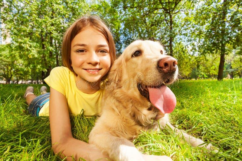 Adolescente con il suo cane che risiede nel parco fotografia stock