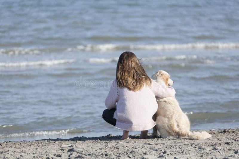 Adolescente con il suo cane su una spiaggia immagini stock