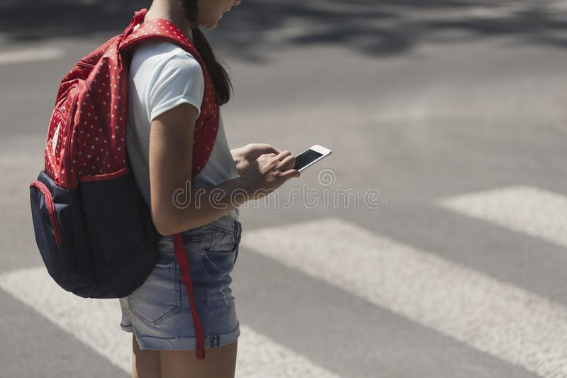 Adolescente con la mochila usando el teléfono durante su manera de la escuela fotografía de archivo libre de regalías