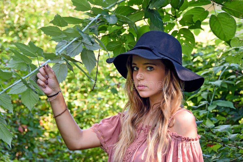 Adolescente con la muchacha del sombrero negro en bosque fotos de archivo