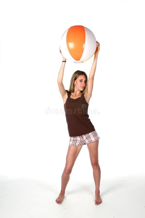 Adolescente con la sfera di spiaggia sul livello immagine stock