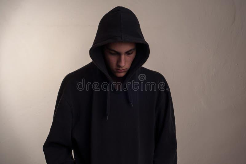 Adolescente con la sudadera con capucha que mira abajo foto de archivo libre de regalías