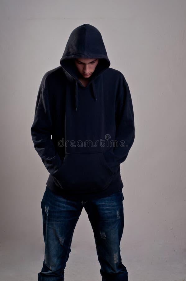 Adolescente con la sudadera con capucha que mira abajo contra una pared gris sucia fotos de archivo