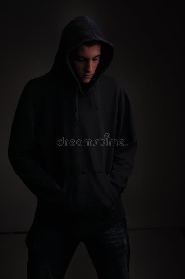 Adolescente con la sudadera con capucha que mira abajo en fondo negro imagen de archivo libre de regalías