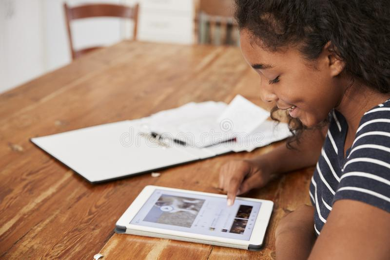 Adolescente con la tableta de Digitaces que revisa para el examen en casa imágenes de archivo libres de regalías