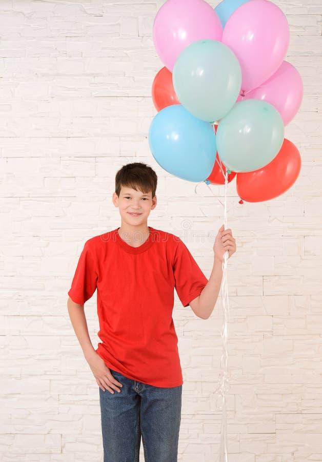 adolescente con las bolas coloridas que se oponen a una pared de ladrillo blanca imagen de archivo libre de regalías