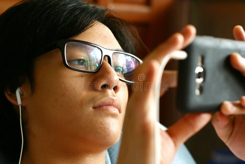 Adolescente con las lentes usando un smartphone fotografía de archivo