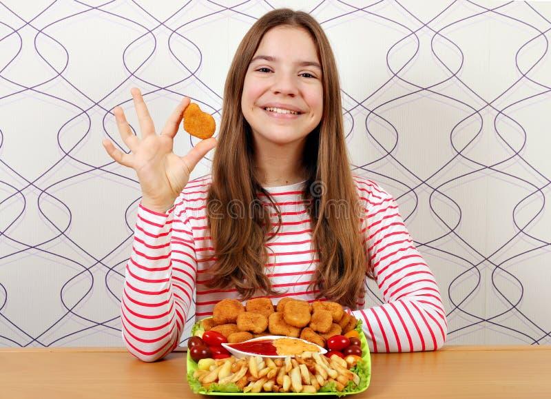 Adolescente con las pepitas de pollo y los alimentos de preparación rápida de las patatas fritas imagen de archivo