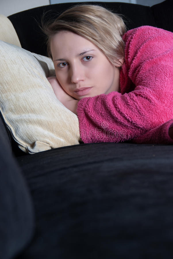 Adolescente con los pijamas en el sofá fotografía de archivo