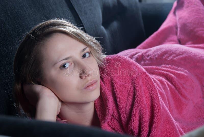 Adolescente con los pijamas en el sofá imagen de archivo libre de regalías