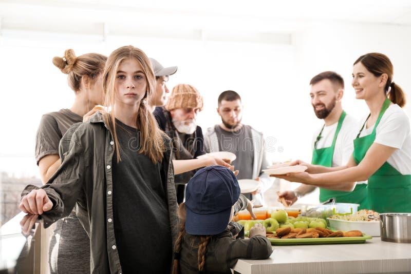 Adolescente con otras personas pobres que reciben la comida de voluntarios imagen de archivo libre de regalías