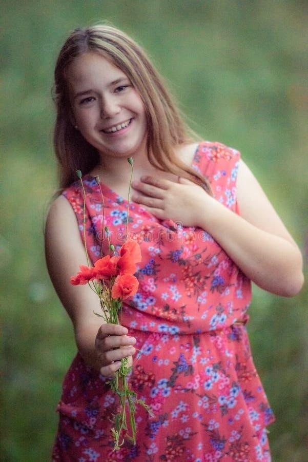 Adolescente con sorridere dei fiori del papavero fotografia stock libera da diritti