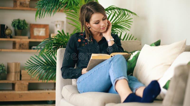 Adolescente concentrado que descansa no sofá na sala de visitas ao ler seu livro novo favorito em casa foto de stock royalty free