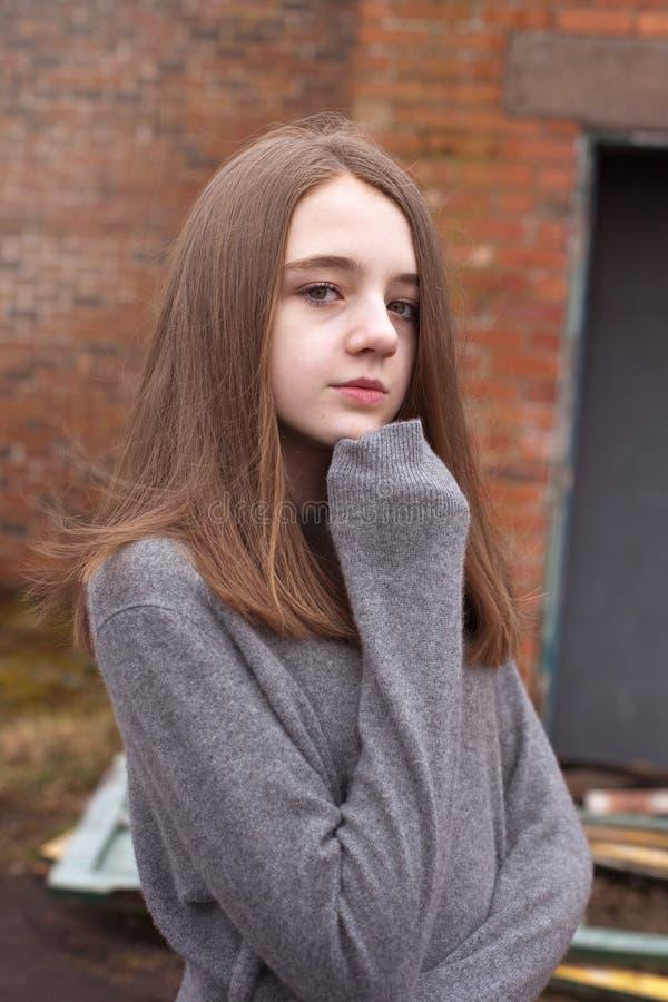 Adolescente consideravelmente novo que huddling em sua ligação em ponte com um derelict fotos de stock
