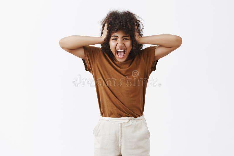 Adolescente contrariée alimentée pissée affligée avec la coupe de cheveux Afro hurlant tenant des mains sur la tête étant peu sat image stock