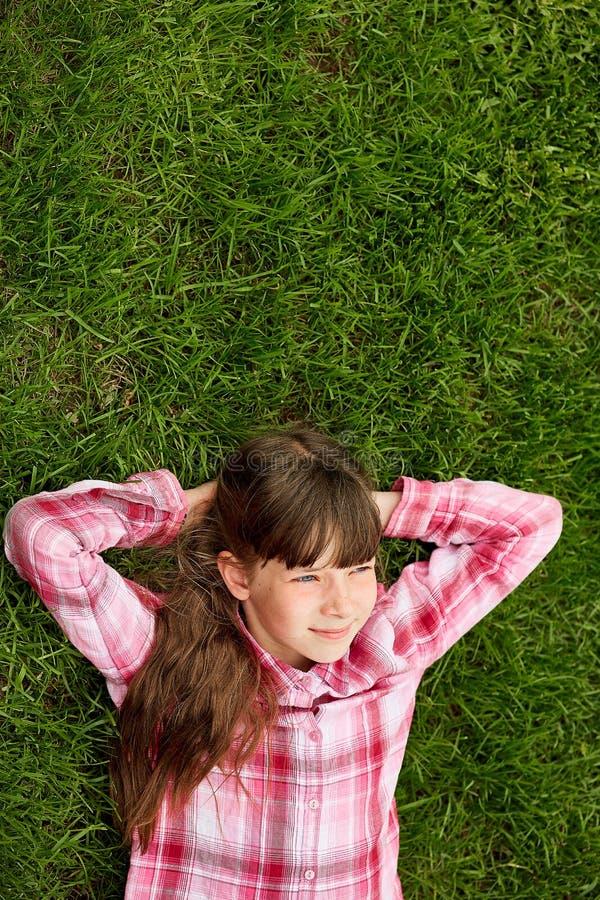 Adolescente décontractée se situant dans l'herbe mode de vie, vacances d'été et concept de personnes photographie stock