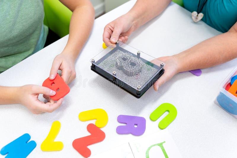 Adolescente d'aiuto del terapista con le difficoltà di apprendimento durante la terapia del bambino Dettaglio della mano di vista fotografie stock
