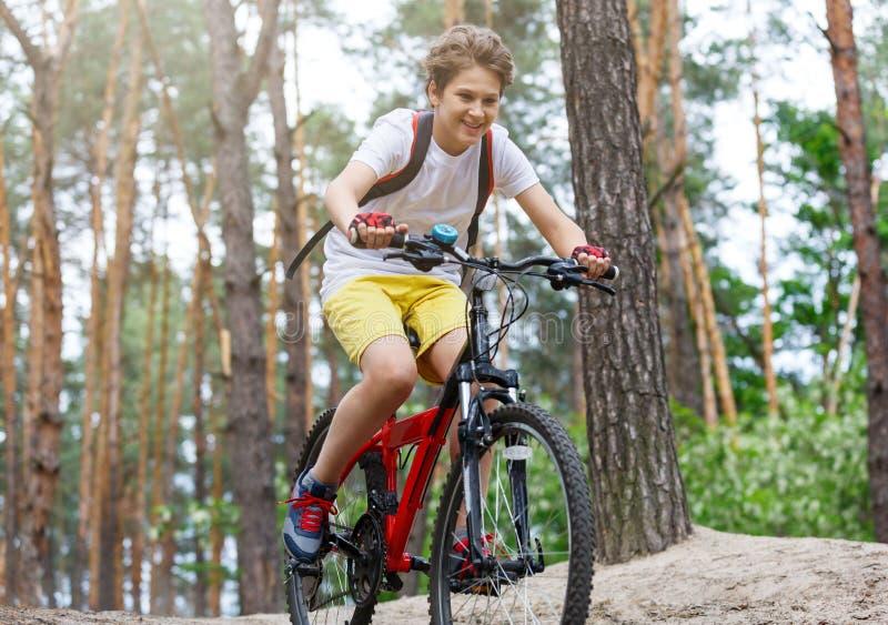 Adolescente da criança na camisa branca de t e short amarelo no passeio da bicicleta na floresta na mola ou no verão Ciclagem de  imagem de stock
