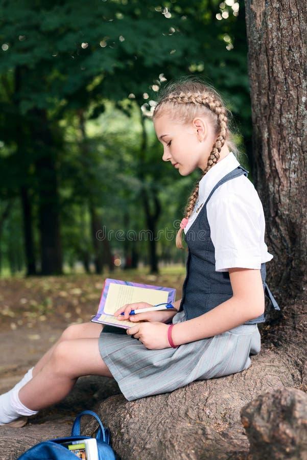 Adolescente da estudante que lê um livro em um parque perto de uma árvore foto de stock royalty free
