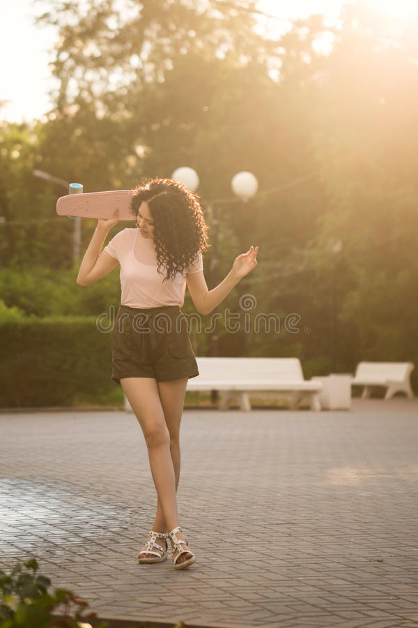 Adolescente da menina com cabelo encaracolado e skate fotografia de stock