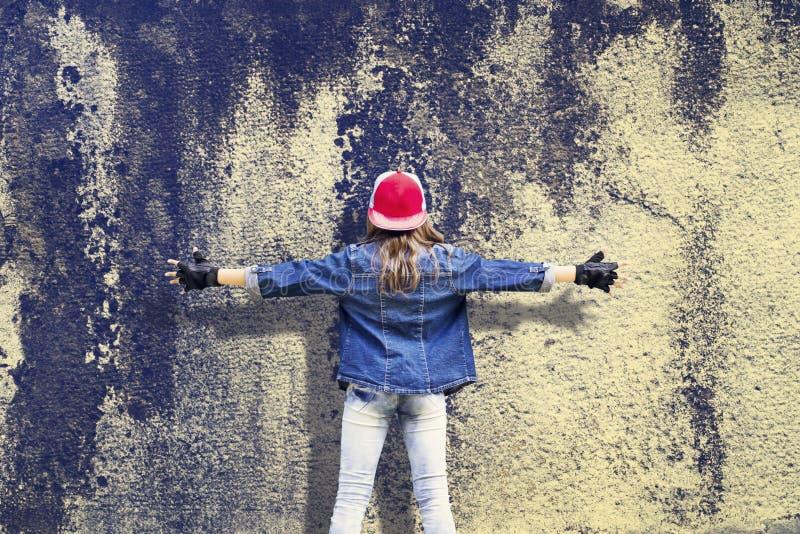 Adolescente da menina com mãos extensamente separadas Roupa da sarja de Nimes Boné de beisebol Em uma parede velha do vintage O c fotografia de stock royalty free