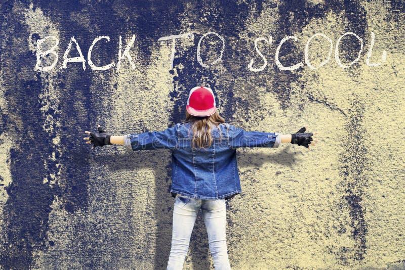 Adolescente da menina com mãos extensamente separadas Roupa da sarja de Nimes Boné de beisebol Na perspectiva do muro de cimento  foto de stock royalty free