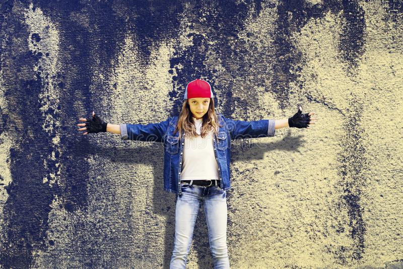 Adolescente da menina com mãos extensamente separadas Roupa da sarja de Nimes Boné de beisebol Na perspectiva do muro de cimento  imagem de stock royalty free