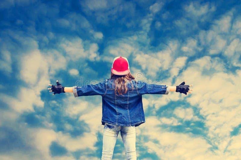 Adolescente da menina com mãos extensamente separadas Roupa da sarja de Nimes Boné de beisebol Na perspectiva de um céu nebuloso  imagem de stock royalty free