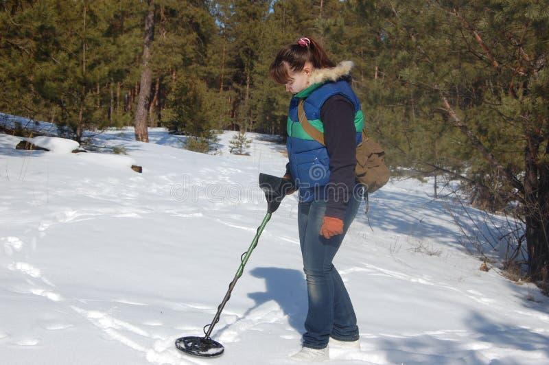 Adolescente da menina com o detector de metais na floresta foto de stock