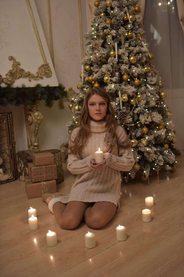 Adolescente da menina em uma camiseta longa com velas em uma árvore de Natal fotografia de stock royalty free