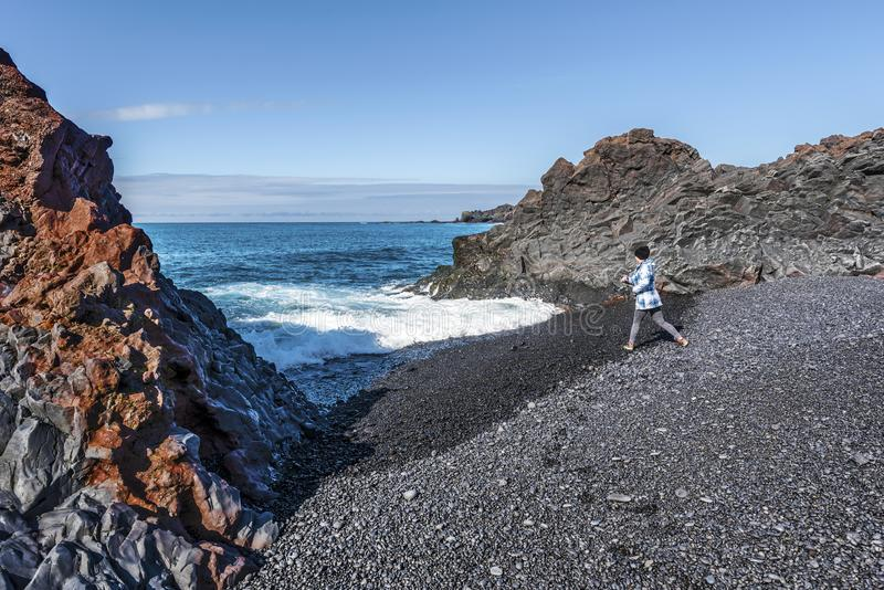 Adolescente da menina na baía de Djupalonssandur da beira entre duas rochas da lava, no parque nacional islandês de Snaefellsjoku foto de stock royalty free