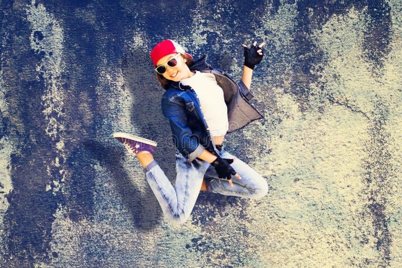 Adolescente da menina no salto Roupa da sarja de Nimes Boné de beisebol Na perspectiva do muro de cimento velho Dança da rua fotos de stock