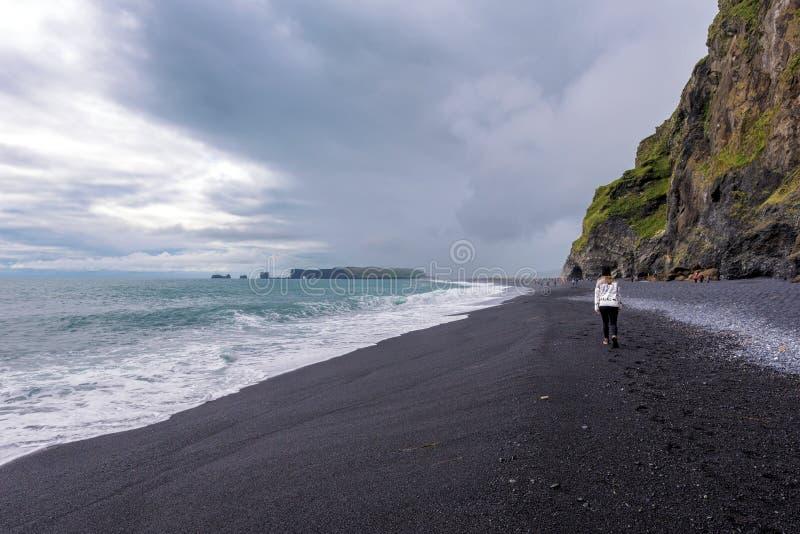 Adolescente da menina que anda ao longo da praia da areia do preto de Reynisfjara em Islândia do sul Montanha de Reynisfjall e de imagens de stock