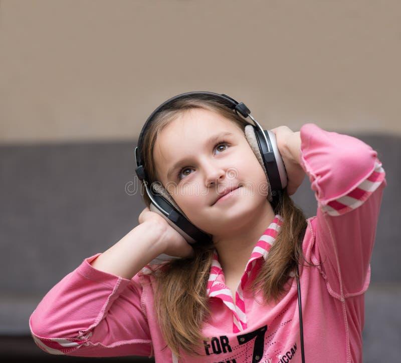 Adolescente da menina que escuta a música com fones de ouvido grandes e que olha acima pensativamente foto de stock