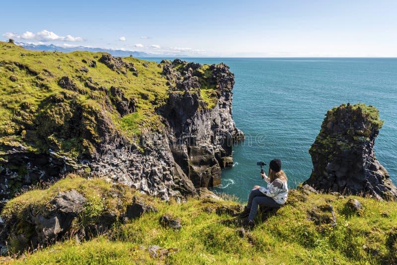 Adolescente da menina que grava a paisagem da península de Snaefellsnes em Islândia ocidental da parte superior do penhasco de Va fotografia de stock royalty free