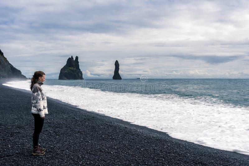 Adolescente da menina que sacia na praia da areia do preto de Reynisfjara em Islândia do sul As pilhas do mar do basalto de Reyni foto de stock royalty free