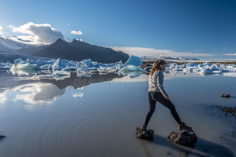 Adolescente da menina que salta sobre rochas na beira do lago da geleira de Fjallsarlon Islândia do sul fotos de stock royalty free
