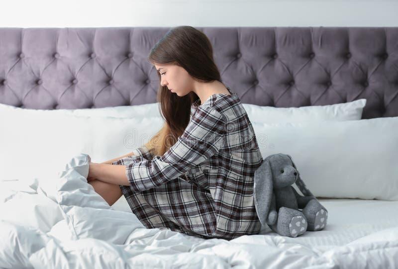 Adolescente da virada com o brinquedo na cama imagem de stock