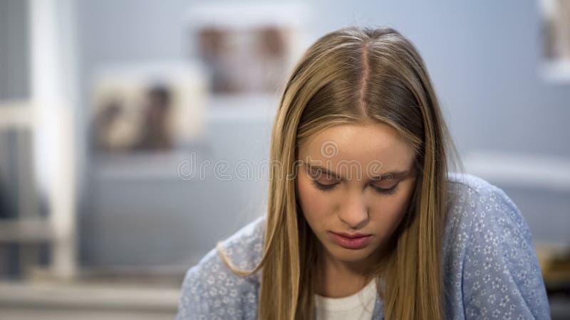 Adolescente da virada que olha duas tiras no teste de gravidez, sentindo desesperado, medo imagens de stock