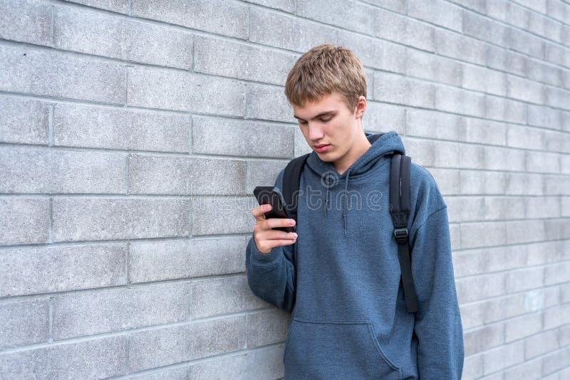 Adolescente da virada que olha seu telefone celular fotografia de stock