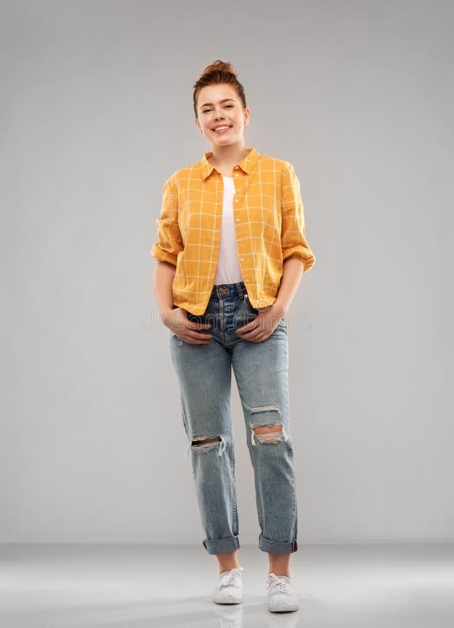 Adolescente dai capelli rossi in camicia e jeans lacerati fotografia stock libera da diritti