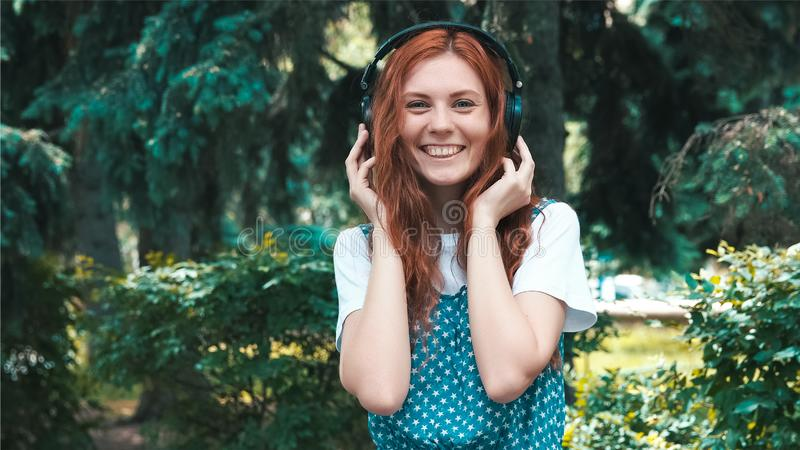 Adolescente dai capelli rossi Freckled ascoltare musica in grandi cuffie immagini stock libere da diritti