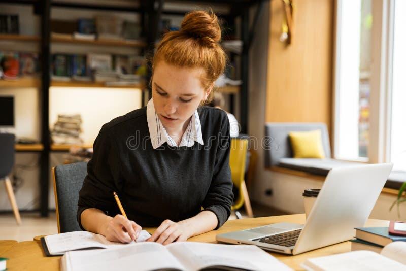 Adolescente dai capelli rossi grazioso che per mezzo del computer portatile fotografia stock libera da diritti