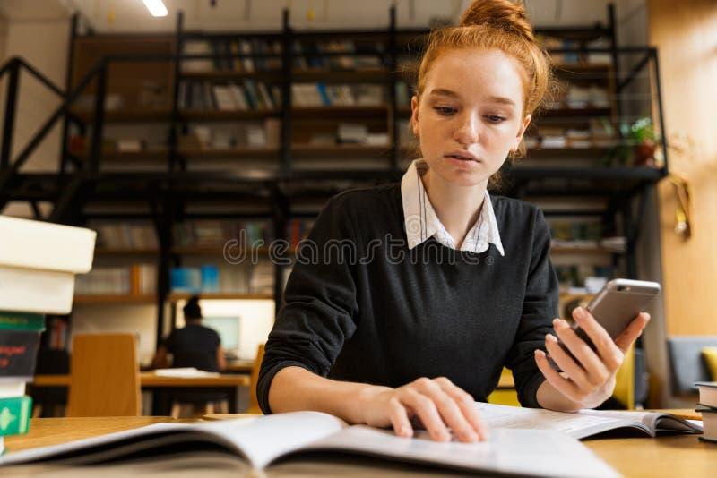 Adolescente dai capelli rossi messo a fuoco che studia alla tavola fotografia stock