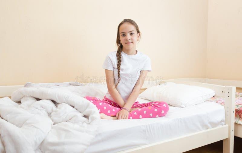 Adolescente dans des pyjamas roses détendant sur le lit photo libre de droits