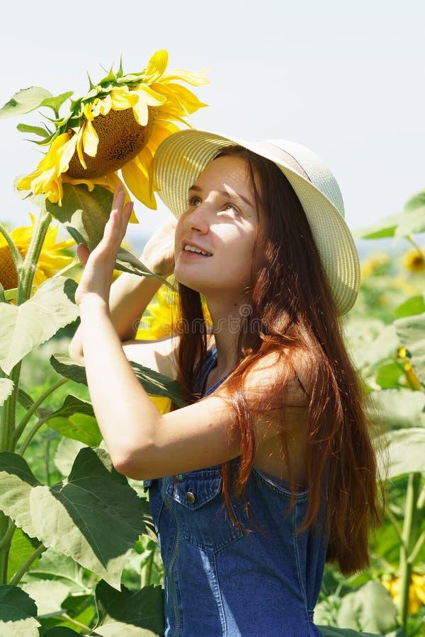 Adolescente dans la robe et le chapeau de denim avec un sourire considérant le tournesol photo stock