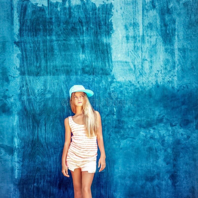 adolescente dans le chapeau avec un mur bleu photo stock