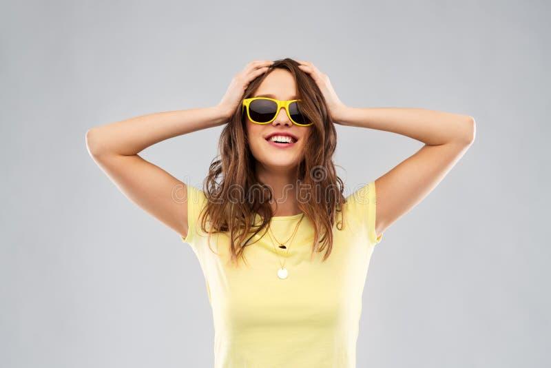 Adolescente dans les lunettes de soleil et le T-shirt jaunes photographie stock